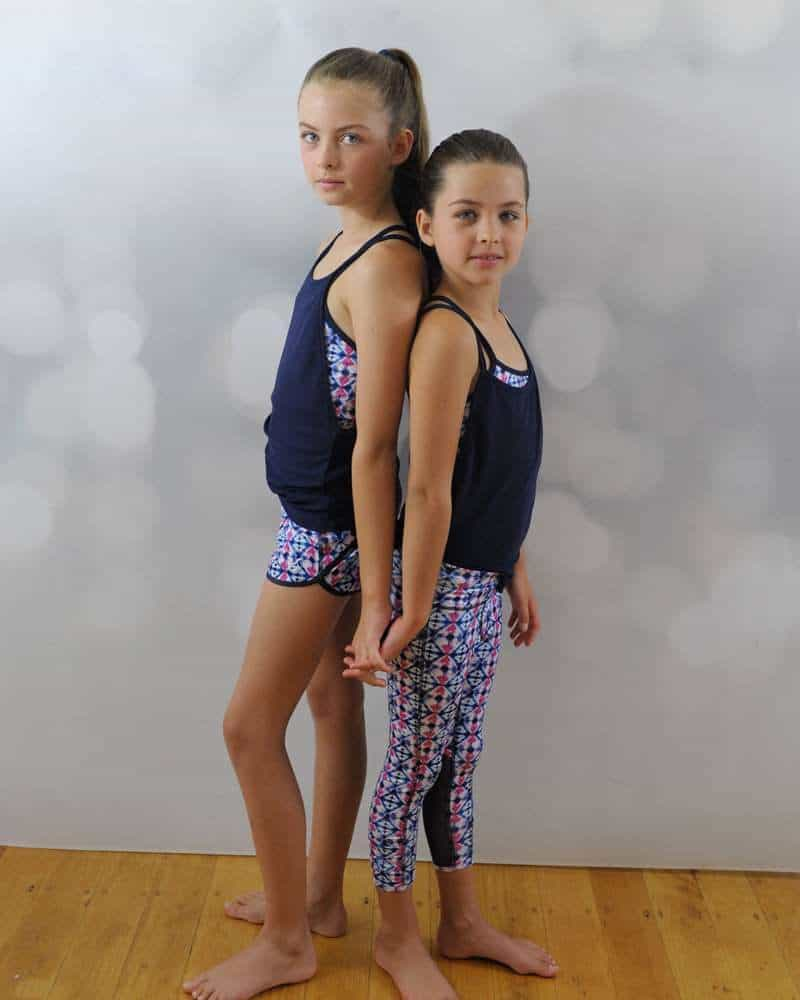 Two young girls standing, wear a pair of gymnastics activewear.