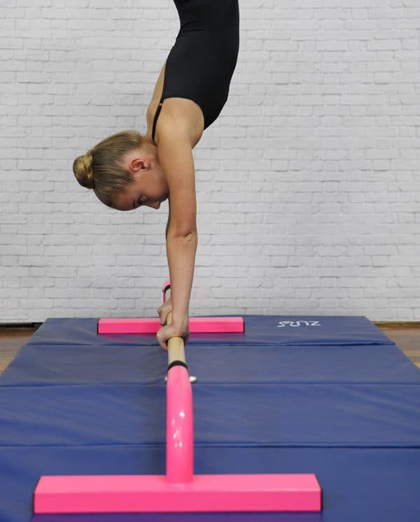 A woman balancing on a pink floor bar.