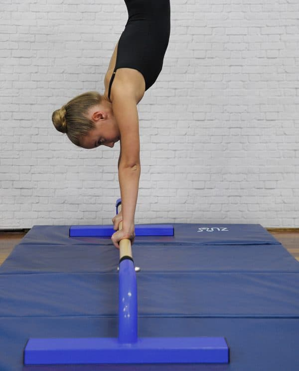 A woman balancing on a blue floor bar.