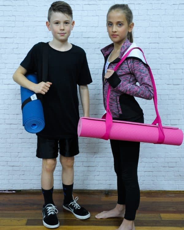 A boy and a girl standing while carrying their gymnast equipment.