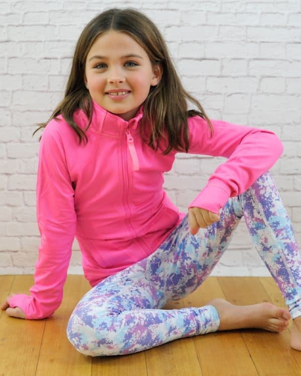 A girl sitting on the floor, wearing pink jacket and printed leggings.