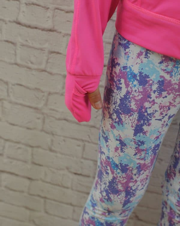 A pink jacket with a thumb hole and printed leggings.