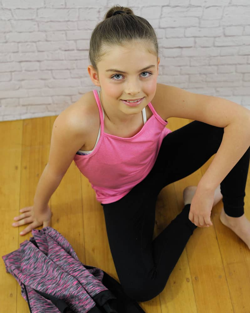A young girl sitting wears a pink sleeveless and black leggings.