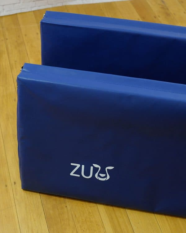 Two pieces of blue tumbling mat with a Zuu brand label.
