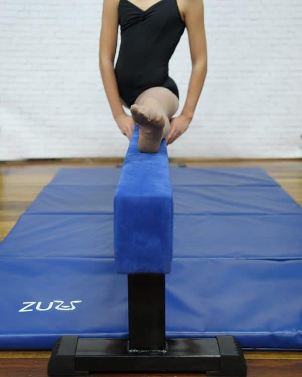 A Blue balance beam with woman on top.