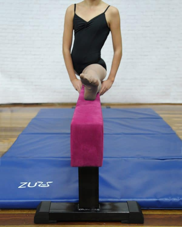 A Pink balance beam with woman on top.