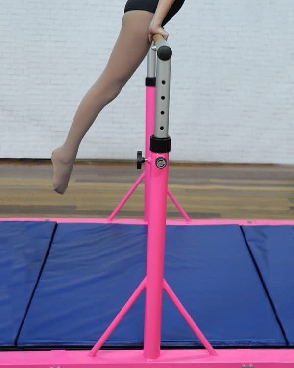 Young gymnast training on Zuu's high bar kit in pink