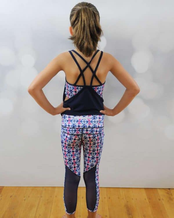 A young girl standing shows the back design of her activewear.