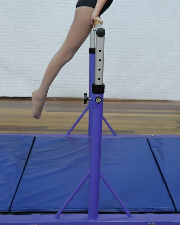 Young gymnasts practising her routine using high fly bar with blue mat for floor protection