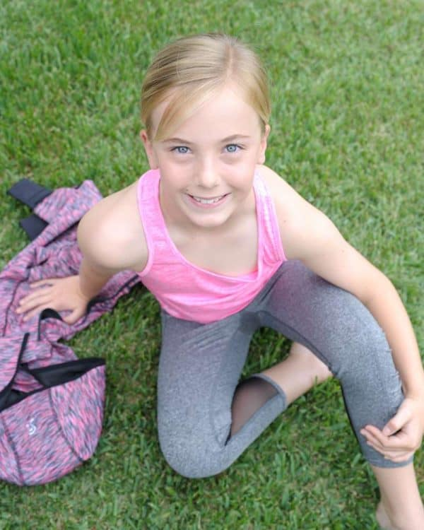 A young girl sitting wears a light pink sleeveless and gray leggings.