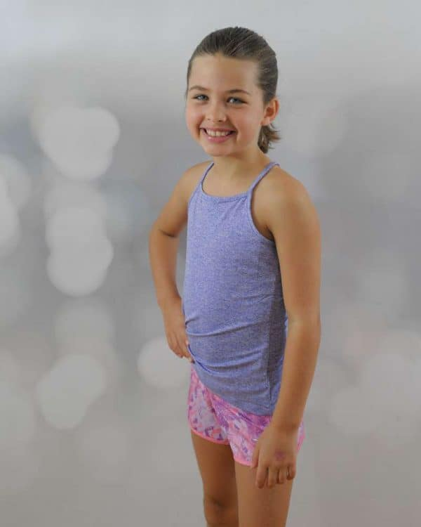 A smiling girl, standing with hand on her waist wearing halter top and pink short thumbnail.
