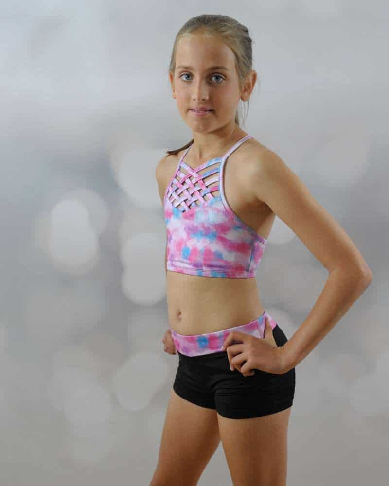 A young girl standing wears a crop top and a short.