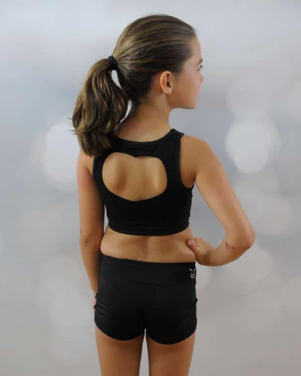A young girl standing shows the back design of her black crop top and a short.