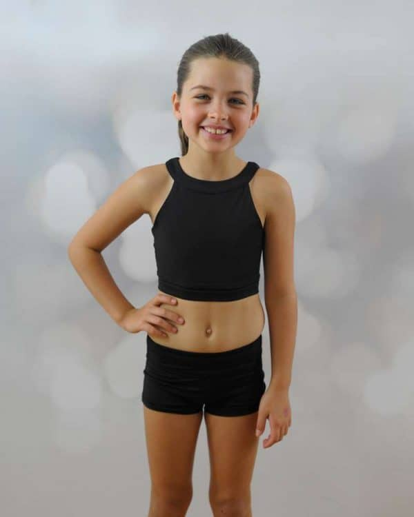 A girl wears a black crop and shorts.