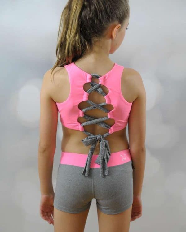 A young girl standing shows the back design of her crop top and shorts.