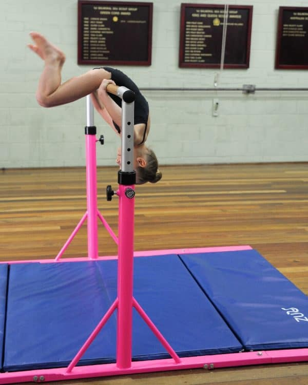 Young gymnast training on the high fly bar in pink