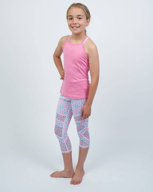 A young girl standing wears a pink sleeveless and leggings.