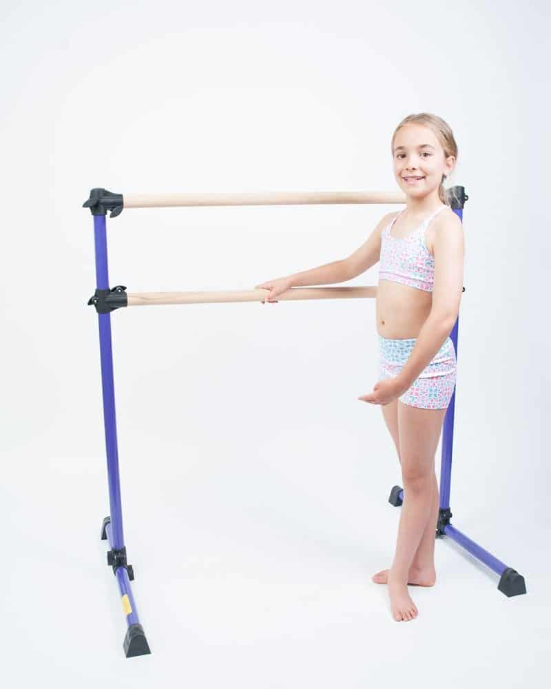 A girl standing beside the double ballet barre with solid wood bar.