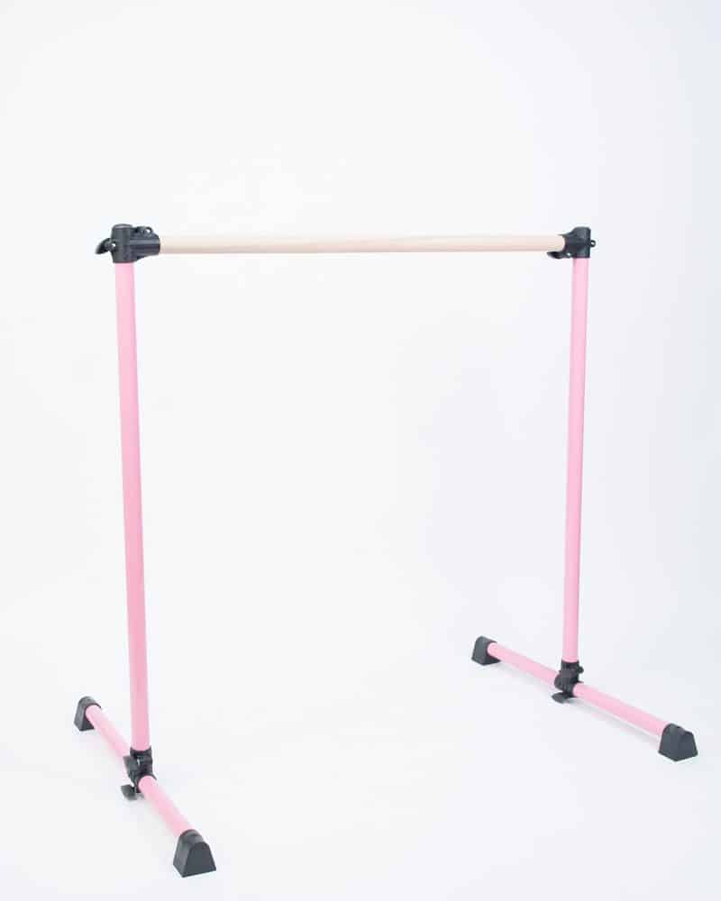 A pink, single freestanding portable ballet barre.