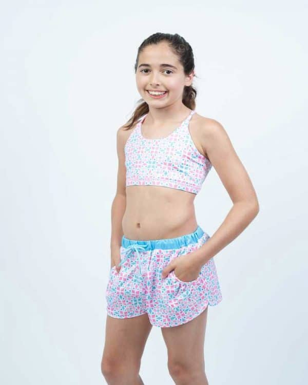 A young girl standing, wears a black and white crop top and short.