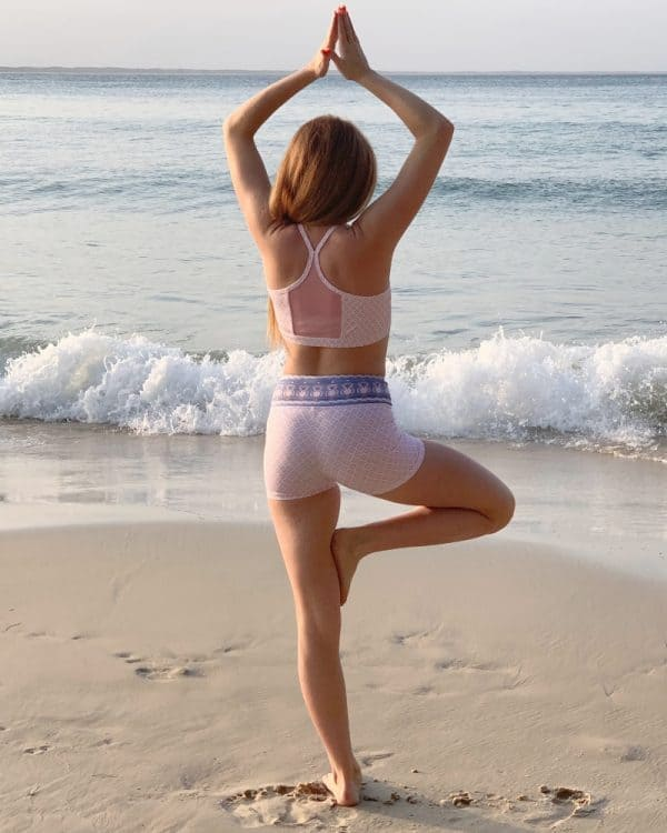 A girl wears a crop top and shorts while performing yoga at the beach.
