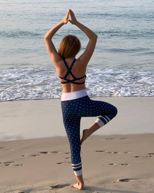 A girl on the beach practicing yoga, wears a pair of navy activewear.